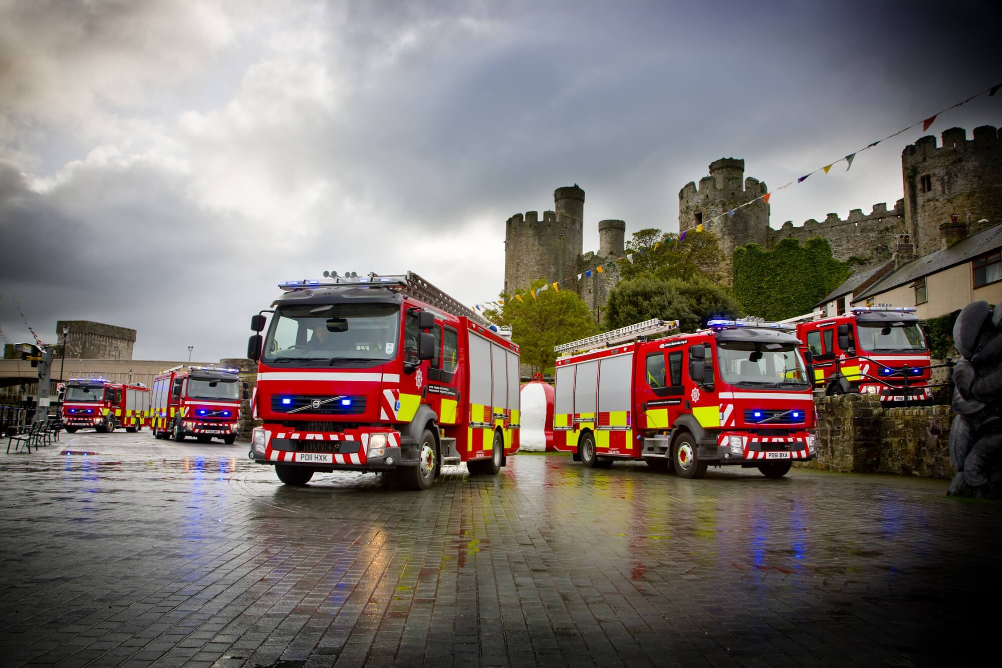 Parked fire engines in front of a castle in Wales to represent the emergency services.